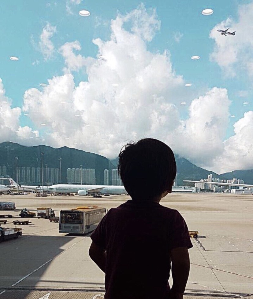Photo of a toddler at an airport looking out the window at airplanes. This is his first move and first goodbye.